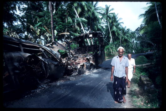 An man walks near a bus destroyed by the JVP near Yariyama, August 1989.(Photo by Robert Nickelsberg/Liaison)