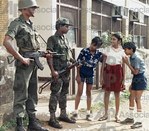 Children look at weapons held by soldiers on guard in Colombo. December 1989. The soldiers are deployed to prevent attacks by JVP radicals who torched 43 passenger buses in central and southern Sri Lanka. (AP Photo)
