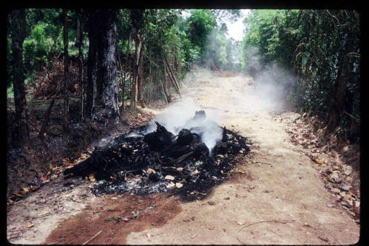 Smoke surrounds burning bodies at a mass grave site in Dikwella, August 1989.(Photo by Robert Nickelsberg/Liaison)