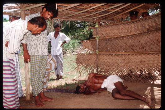 Villagers looking at a victim killed by unknown groups. April 1989(Photo by Robert Nickelsberg/Liaison)