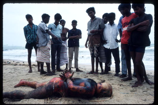 Onlookers examining a burnt body that washed up in Negombo. August 1989.(Photo by Robert Nickelsberg/Liaison)