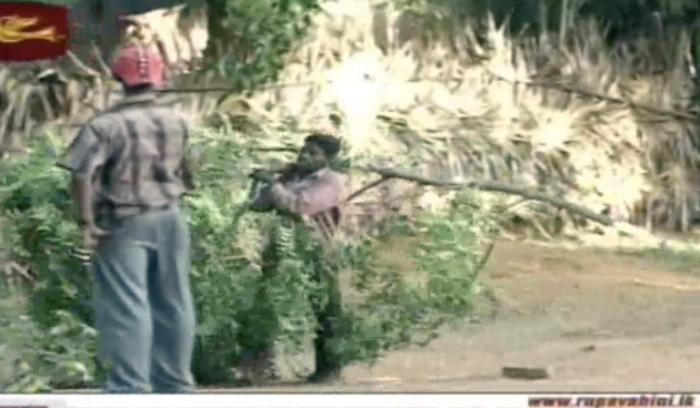 Civilian helper helping to camouflage an LTTE personnel carrier, overseen by an armed LTTE cadre dressed in civilian clothes